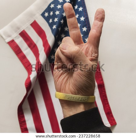 victory sign with veterans support bracelet - stock photo