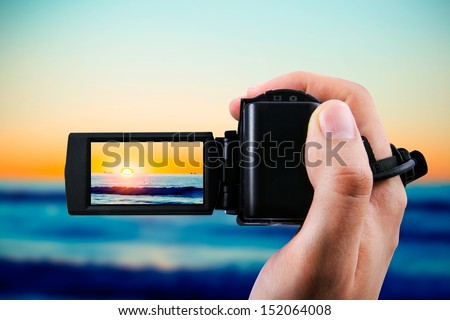 Video camera or camcorder recording sunset - stock photo