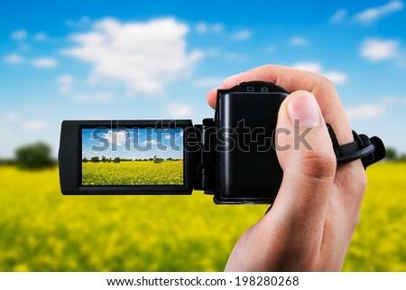 Video camera or camcorder recording yellow field and blue sky - stock photo