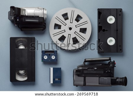 Video cameras, VHS and Mini cassettes and a film roll well arranged over blue background, above view - stock photo