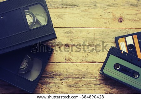 video cassettes and audio cassettes on a wooden table, retro style - stock photo