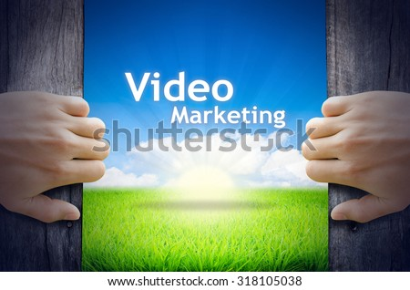 Video Marketing. Hands opening a wooden door then found a texts floating among new world as green grass field, Blue sky and the Sunrise. - stock photo