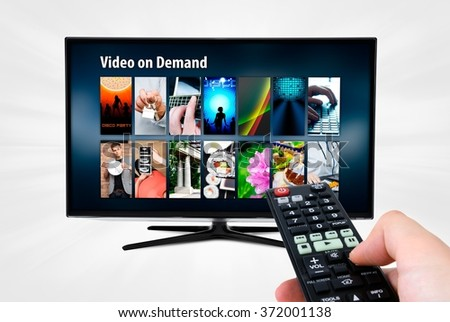 Video on demand VOD service on smart TV. Remote control in hand.
