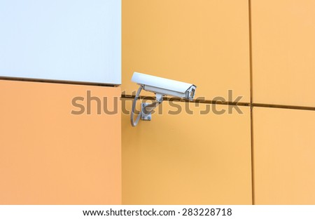 video surveillance camera hanging on the wall of a building