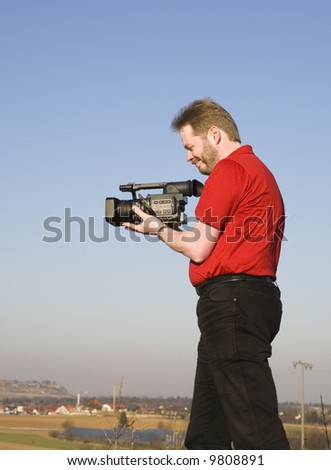 Videographer shooting handheld footage with prosumer camcorder - stock photo