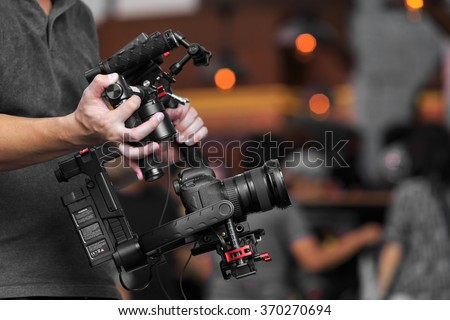 videographer using steady cam, Professional equipment helps to make high quality video - stock photo
