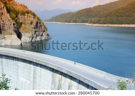 Vidraru Dam on Arges River in Transylvania, Romania. Hydro electric power station. Retro tone color effect - filtered colors style. - stock photo