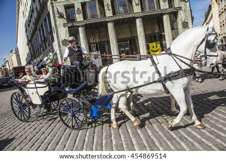 VIENNA, AUSTRIA - APR 27, 2015: Traditional horse riding in a Fiaker through the city center in Vienna, Austria. The numer of horse riders is limited and they have a special licence.