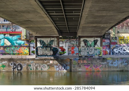 "VIENNA, AUSTRIA - April 13, 2015:  Graffiti under ""Marienbruecke"", a bridge over Danube Canal (Donaukanal). The embankment walls of Danube Canal form a giant canvas for street artists. - stock photo"