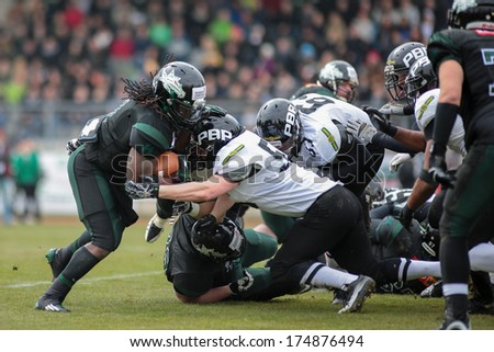 VIENNA,  AUSTRIA - APRIL 6 LB Dan Krejbich  (#50 Panthers) and RB Tunde Ogun (#1 Dragons) fight for the ball during the AFL football game on April 6, 2013 in Vienna, Austria.