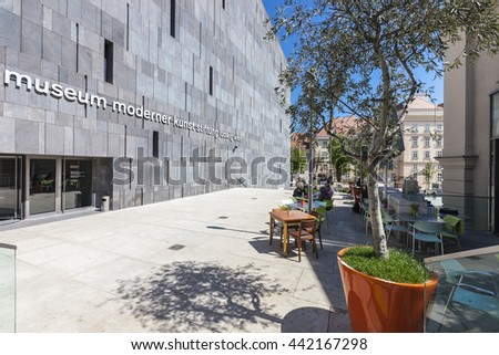 VIENNA, AUSTRIA - APRIL 29, 2016: Some people enjoy a sunny afternoon beside the Museum of Modern Art Stiftung Ludwig at the Museumsquartier which is the eighth largest cultural area in the world. - stock photo
