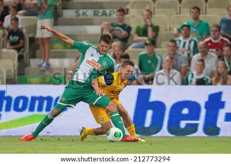 VIENNA, AUSTRIA - AUGUST 8 Christopher Trimmel (#28 Rapid) and Pablo de Blasis (#32 Asteras) fight for the ball at a UEFA Europa League game on August 8, 2013 in Vienna, Austria. - stock photo