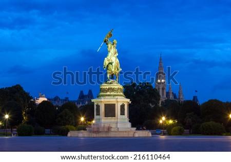 VIENNA, AUSTRIA - AUGUST 4, 2013: Monument dedicated to Archduke Charles of Austria (Erzherzog Karl) ridding a horse and the city hall (Rathause) in Vienna, Austria. - stock photo