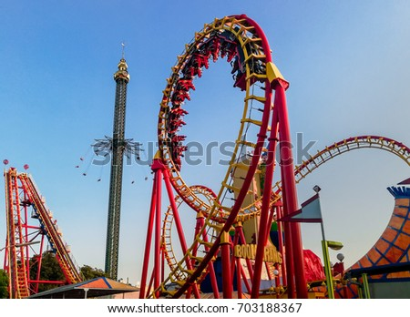 Vienna, Austria, August 2017: Prater amusement park with roller coaster and carousel entertaining the visitors  in a colorful settings
