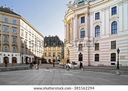 VIENNA, AUSTRIA - FEBRUARY 6, 2016: Horse-drawn carriage or Fiaker, popular tourist attraction, on Michaelerplatz in Vienna against backdrop of Hofburg Palace