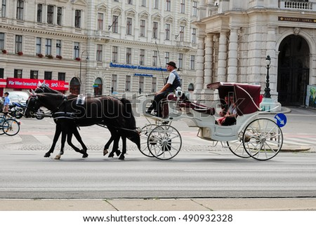 VIENNA, AUSTRIA - JULY 18, 2015: Horse-drawn carriage for sightseeing takes tourists in the Hofburg Imperial Palace in Vienna