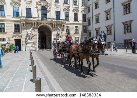 VIENNA, AUSTRIA - JULY 21: people have a ride in the fiaker and pass the Hofburg on July, 21,2013 in Vienna. The fiaker first was build in the 18 century in the street Rue de Saint Fiacre.