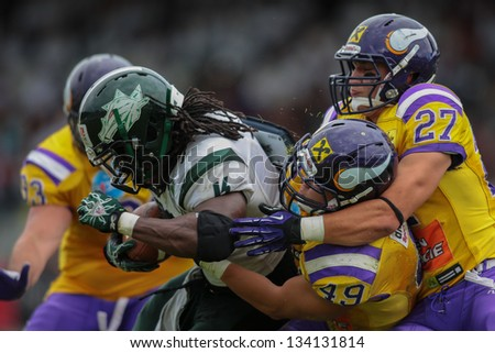 VIENNA, AUSTRIA - JULY 15 RB Tunde Ogun (#1 Dragons) is tackled by LB Simon Blach (#49 Vikings) and LB Marcus Greber (#27 Vikings) on July 15, 2012 in Vienna, Austria. - stock photo