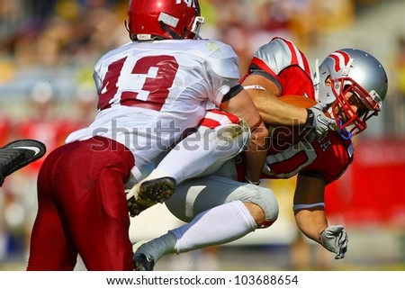 VIENNA, AUSTRIA - JUNE 5 RB Mario Nerad (#20 Austria) is tackled by DB Bobby Short (#43 Rose Hulman) on June 5, 2011 in Vienna, Austria. Rose Hulman College beats Team Austria 35:34 in overtime. - stock photo