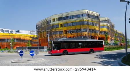 VIENNA, AUSTRIA, June 13, 2015: Vienna University of Economics and Business. Futuristic architecture designed by Zaha Hadid. Wirtschaftsuniversitat Wien WU. Exterior details. View on campus, city bus. - stock photo