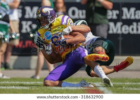 VIENNA, AUSTRIA - JUNE 22, 2014: WR Laurinho Walch (#6 Vikings) is tackled by S Sascha Verhoeven (#3 Dragons). - stock photo