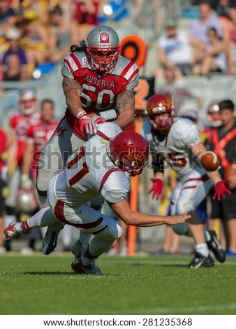 VIENNA, AUSTRIA - MAY 26, 2014: LB Ramon Azim (#50 Austria) makes a tackle in match against Denmark during the EFAF European Championships 2014 in Austria. - stock photo