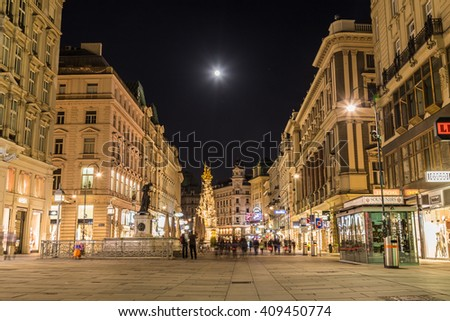 VIENNA, AUSTRIA - 22ND APRIL 2016: A view along the Graben in Vienna at night. The outside of buildings and the blur of people can be seen. - stock photo
