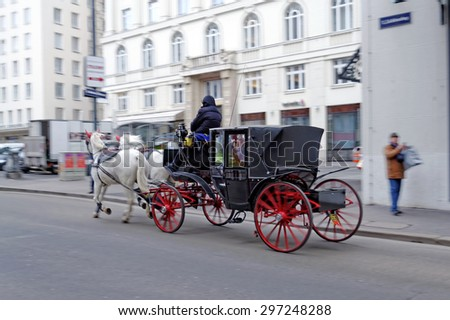 VIENNA, AUSTRIA - NOVEMBER 22, 2013: Tourists have a ride in the fiaker and pass the narrow streets of the historic central part of downtown Vienna.  - stock photo