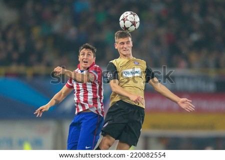 VIENNA, AUSTRIA - OCTOBER 22 Emir Dilaver (#27 Austria) and Christian Rodriguez (#11 Atletico) fight for the ball at a UEFA Champions League game on October 22, 2013 in Vienna, Austria. - stock photo