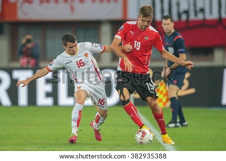 VIENNA, AUSTRIA - OCTOBER 12, 2014: Lukas Hinterseer (#19 Austria) and Vladimir Jovovic (#16 Montenegro) fight for the ball in an European Championship qualifying game. - stock photo