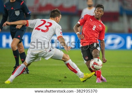 VIENNA, AUSTRIA - OCTOBER 12, 2014: Marko Simic (#23 Montenegro) and David Alaba (#8 Austria) fight for the ball in an European Championship qualifying game. - stock photo