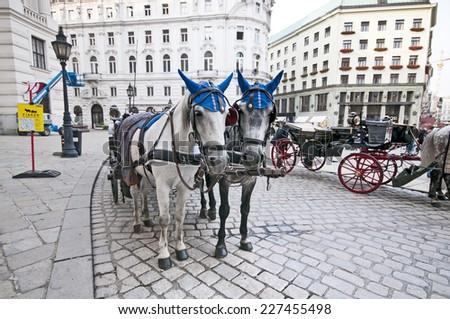 VIENNA, AUSTRIA - OCTOBER 08, 2014: Traditional old-fashioned fiacres at  Michaelerplatz near Hofburg of Vienna, Austria.  - stock photo