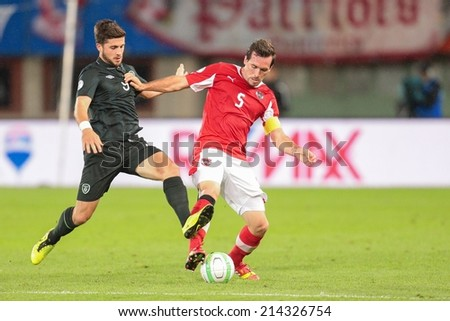 VIENNA, AUSTRIA - SEPTEMBER 10 Christian Fuchs (#5 Austria) and Shane Long (#9 Ireland) fight for the ball at a World Cup Qualifying game on September 10, 2013 in Vienna, Austria. - stock photo