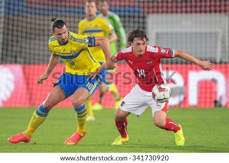 VIENNA, AUSTRIA - SEPTEMBER 9, 2014: Julian Baumgartlinger (#14 Austria) and Zlatan Ibrahimovic (#10 Sweden) fight for the ball in an European Championship qualifying game. - stock photo