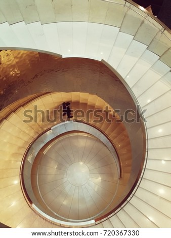 Vienna, Austria, September 2017: Melia hotel interior staircase shining with gold and marble and the shilouette of a man walking down the stairs