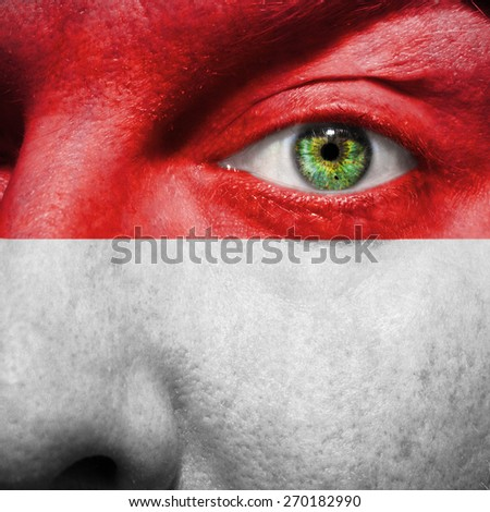 Vienna flag painted on a man's face to support his city Vienna - stock photo