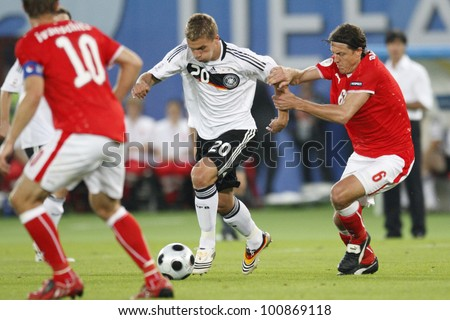 VIENNA - JUNE 16:  Lukas Podolski of Germany controls the ball against Austria's Rene Aufhauser during a UEFA Euro 2008 match June 16, 2008 in Vienna, Austria.  Editorial use only. - stock photo