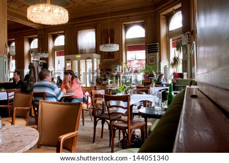 VIENNA - JUNE 5: People inside the old cafe Westend in typical Viennese style with historical chairs and interior directly to the opposite of Westbahnhof station on June 5, 2013 in Vienna, Austria - stock photo