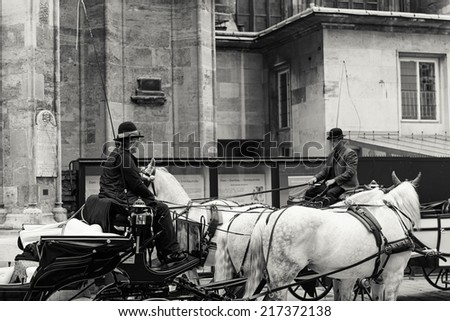 VIENNA - JUNE 21: Traditional carters (fiakers) on their horse-drawn carriages waiting for client in front of St. Stephen's cathedral in central Vienna, Austria, on June 21, 2014.