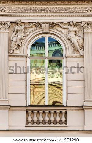 Vienna Opera reflecting in the window of typical moudeling facade - stock photo