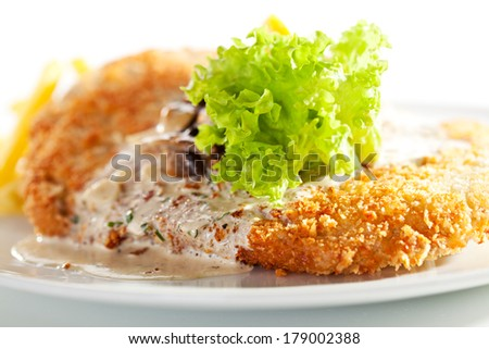 Vienna Schnitzel Served with Mushroom Sauce and French Fries - stock photo