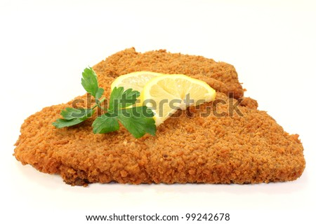 Viennese-style schnitzel with lemon and parsley - stock photo