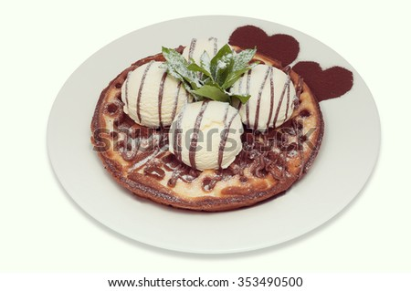 Viennese waffles with four balls of vanilla ice cream and mint on white plate