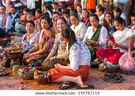 VIENTIANE,LAOS - NOV 21 : Lao people assembled to give offering to Buddhists monks early in the morning on Nov 21, 2010 during That Luang Festival is held on the full moon in November every year. - stock photo