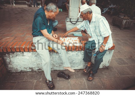 VIETNAM, HANOI - 23 SEPTEMBER 2013: local residents relax and play checkers on the island of the Lake of the Restored Sword