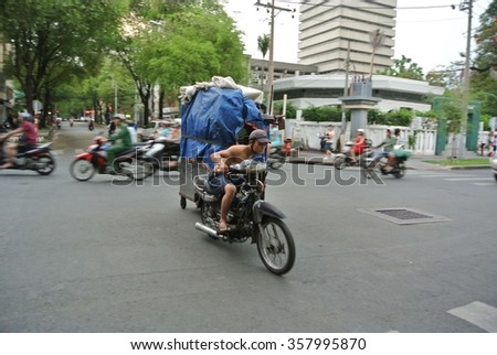 Vietnam, Ho Chi Minh, Saigon, March 2014: A man rushing to deliver his big parcel on a small motorcycle which is the main transport in the buzy street of Saigon.Blur out focus effect due to movement.  - stock photo