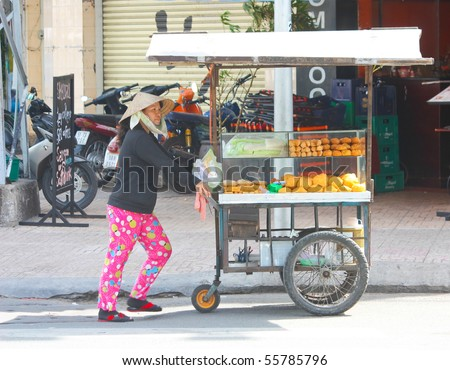VIETNAM - JUNE 10: A Vietnamese bread stall owner pushes her make shift wagon stall along the streets. June 10, 2010 Ho Chi Minh City, Vietnam