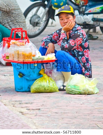 VIETNAM - JUNE 10: A Vietnamese street food vendor having a depressed look while sitting on the road side. June 10, 2010 Ho Chi Minh City, Vietnam - stock photo