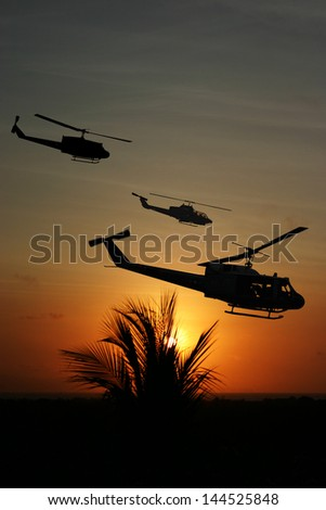 Vietnam War 'style' image circa 1970 three helicopters flying over South Vietnam looking for the North Vietnamese Army. (Artist's Impression) - stock photo