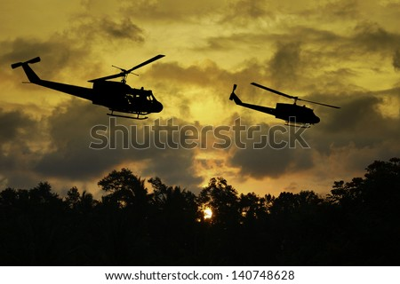 Vietnam War 'style' image of two helicopters flying low over the jungle canopy at sunset time. (Artist's Impression) - stock photo